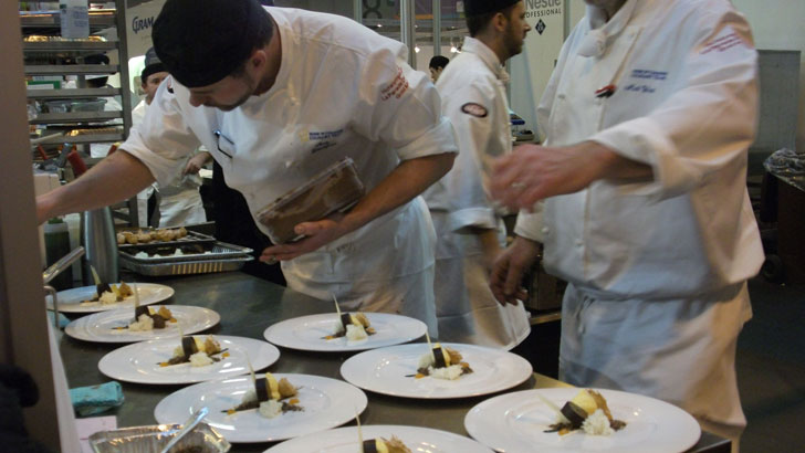 A chef puts the finishing touches to dishes to be served at La
